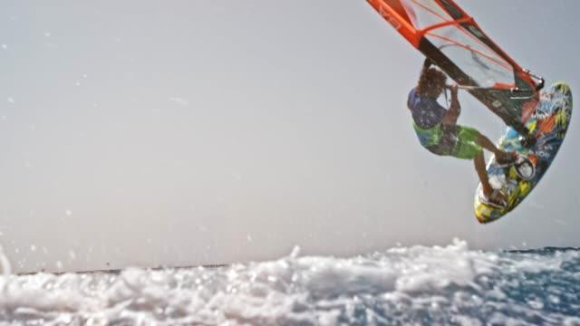 stockvideo's en b-roll-footage met slo mo windsurfer doen een sprong met zijn windsurf - windsurfen
