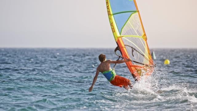 stockvideo's en b-roll-footage met slo mo windsurfer uitbreiding van zijn hand in het water tijdens het rijden - windsurfen
