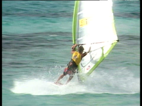 stockvideo's en b-roll-footage met windsurfer performs series of twists turns and jumps including chacho then sails away professional windsurfers association world tour 2003 bonaire... - sportkampioenschap