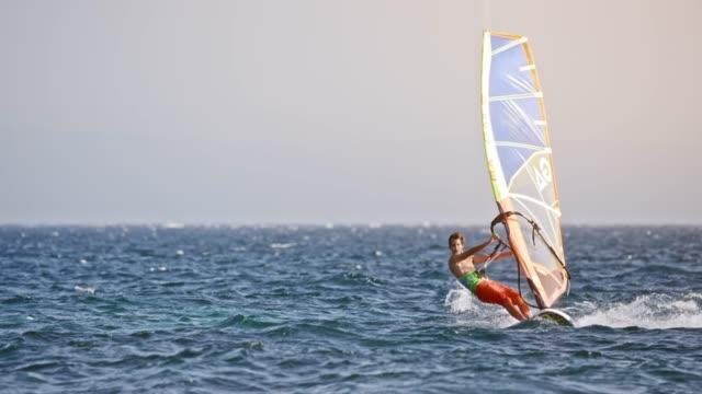 SLO MO Windsurfer riding at sea in sunshine
