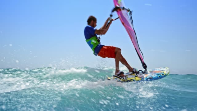 slo mo windsurfer riding in sunshine - aquatic sport stock videos & royalty-free footage