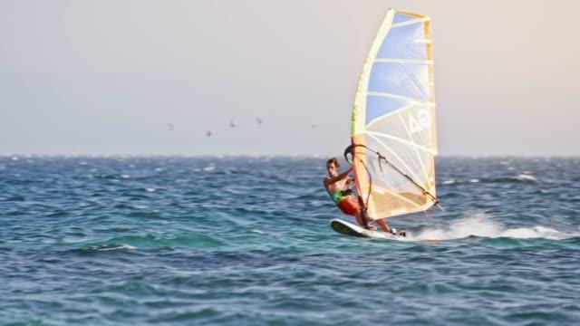 stockvideo's en b-roll-footage met windsurfer rijden in winderig weer - windsurfen