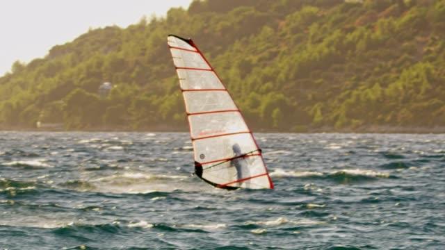 stockvideo's en b-roll-footage met slo mo windsurfer rijden op de golven - windsurfen