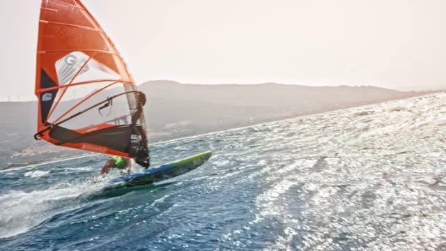 SLO MO Windsurfer riding with suns shining in the background