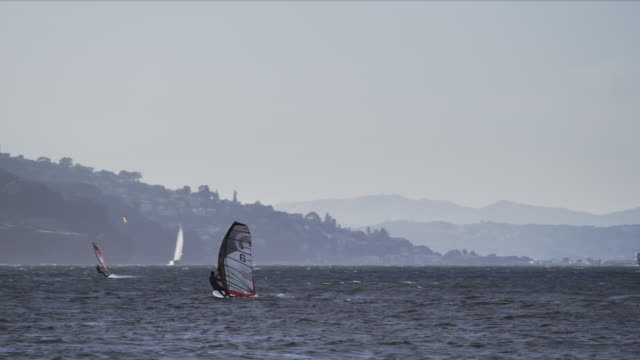 windsurfer speeds away from camera out into san francisco bay - san francisco bay stock videos & royalty-free footage