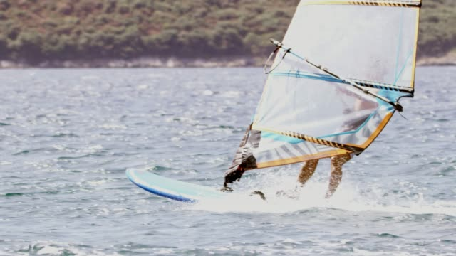 slo mo windsurfer surfing on the ocean - surfing stock videos & royalty-free footage