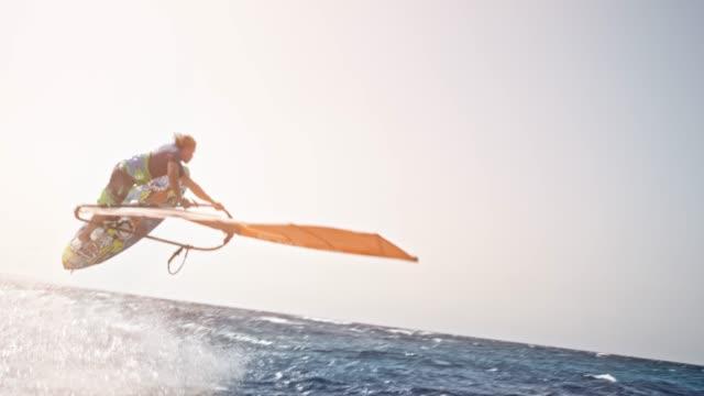 stockvideo's en b-roll-footage met slo mo windsurfer probeert te springen in de lucht in de zon maar falls - windsurfen