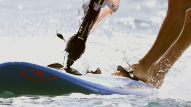 stockvideo's en b-roll-footage met slo mo windsurfer de benen als hij surfen op de oceaan - windsurfen