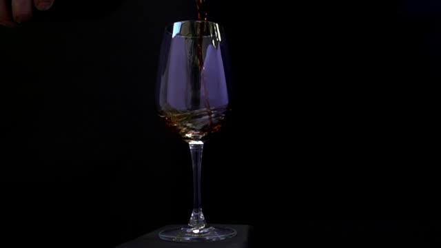 vídeos de stock e filmes b-roll de wine being poured in to a wine glass in slow motion and the camera revolves around it. - david ewing