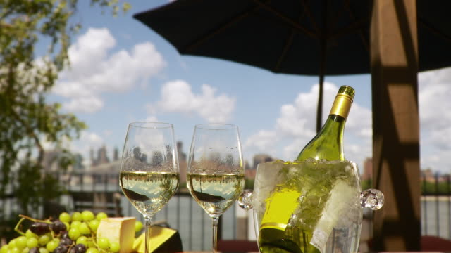 vídeos de stock e filmes b-roll de cu td wine bottle and glasses on table with manhattan skyline behind / new york city, usa - balde