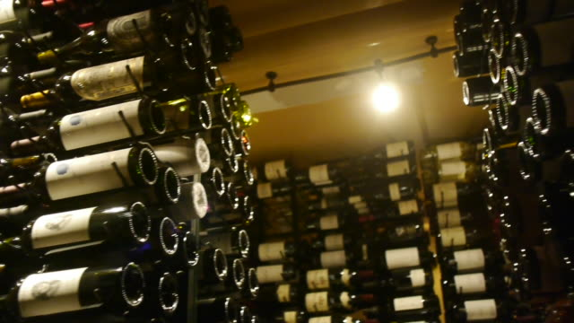 wine bottles are stacked in a low lit wine cellar. - wine bottle stock videos & royalty-free footage