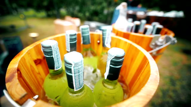 wine bottles in a wooden bucket served at the bar counter in outdoor party. - cooler container stock videos and b-roll footage