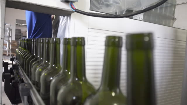 wine bottles on the conveyor belt at cooperativa vinícola são joão, southern brazil. - bundesstaat rio grande do sul stock-videos und b-roll-filmmaterial