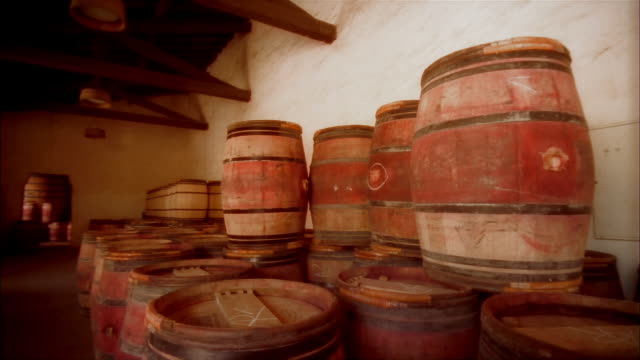 wine casks stacked in cellar at chateau margaux / pan down to cask with name of winery branded on lid / margaux, medoc, france - wine cask stock videos and b-roll footage
