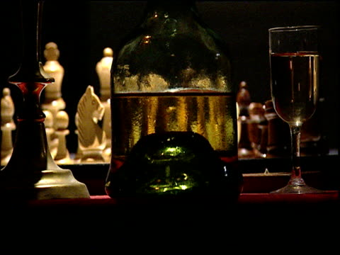 Wine glass and bottle obscuring chess game in background