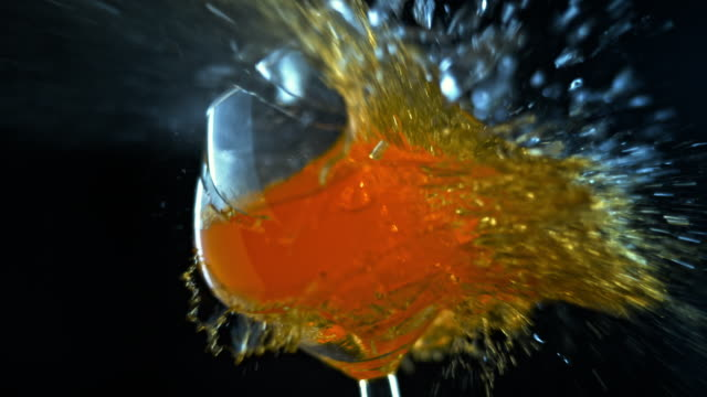 slo mo ld wine glass filled with orange liquid shattering - cold drink stock videos & royalty-free footage
