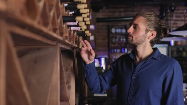 Wine Restaurant. Handsome Man Choosing Wine Bottle On Shelf