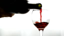 Wine. Seamless cinemagraph video. Red wine pouring in wine glass over dark background. Rose wine pouring from the bottle. Slow motion