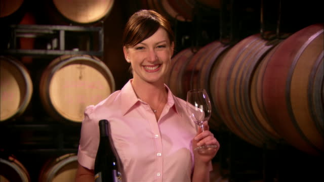 MS Wine server holding wine bottle and empty wineglass near casks in wine cellar / Paso Robles, California, USA
