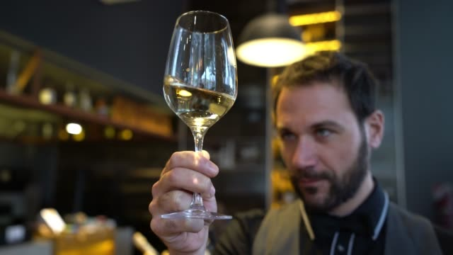 Wine steward looking at the color of a white wine in a glass while shaking it