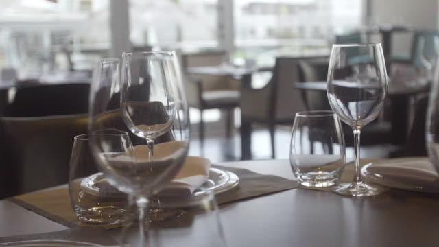 wineglasses and plates on restaurant table - ワインバー点の映像素材/bロール
