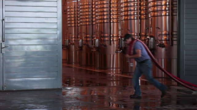 Winemaker drags hoses past stainless tanks at Ruca Malen winery.