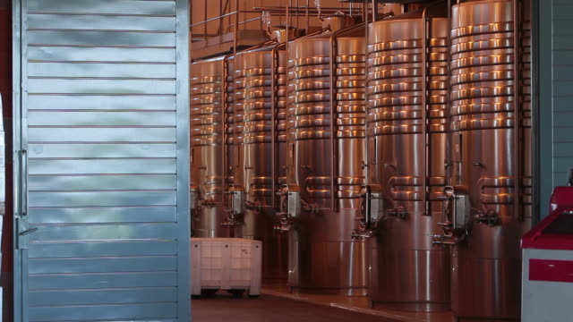 Winemaker transports a bin of wine past stainless tanks.