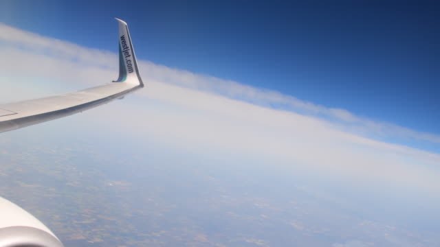 Wing of a passenger plane flying in a quiet blue sky with clouds in the horizon Aviation is the main way of transport for tourism
