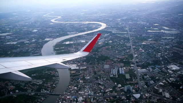 wing of aircraft flying over city and river - photograph stock videos & royalty-free footage