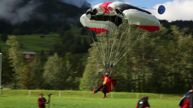 Wing suit flier comes in for landing, in green meadow
