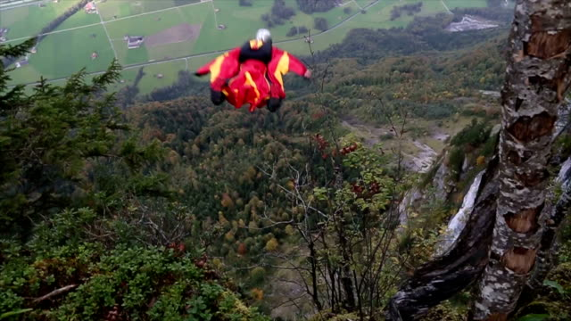 Wing suit flier descends from cliff, aiming for valley below