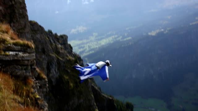 Wing suit flier descends from cliff to valley below