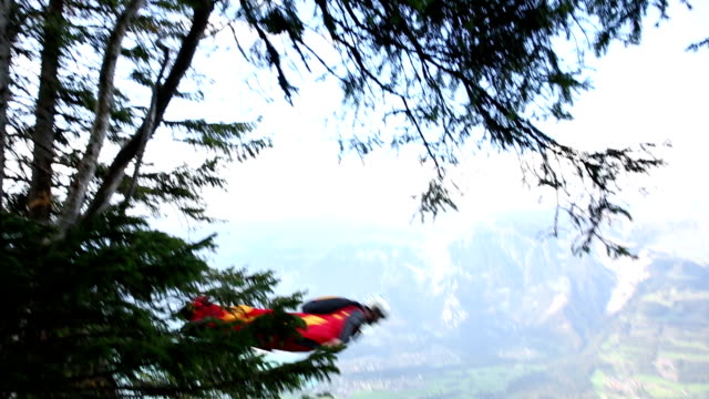 Wing suit flier descends from edge of cliff