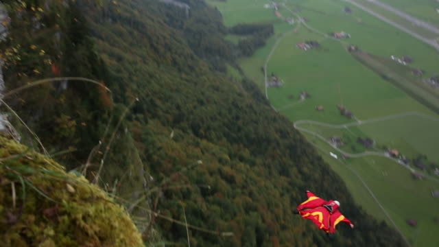 Wing suit flier jumps from cliff and soars above valley below