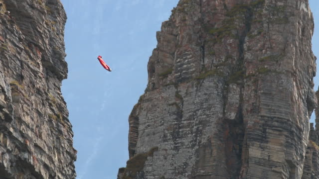 Wing suit flier jumps from cliff soars above valley below