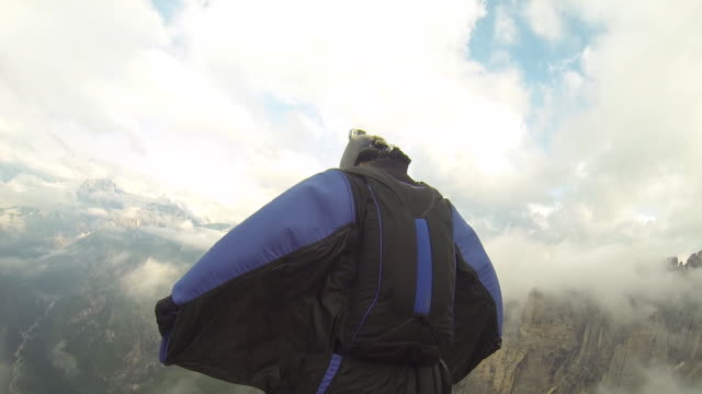 vidéos et rushes de wing suit flier jumps from cliff, soars above valley below - infini