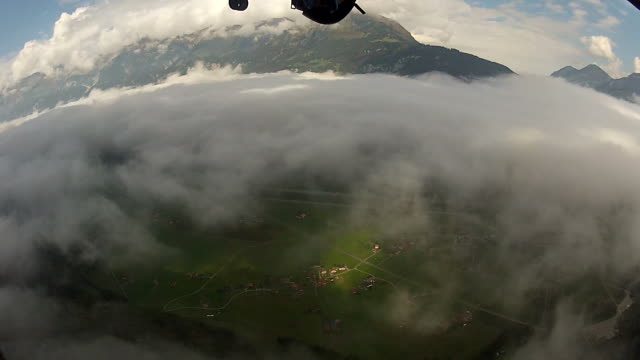 POV of wing suit flier soaring above valley and targeting landing spot