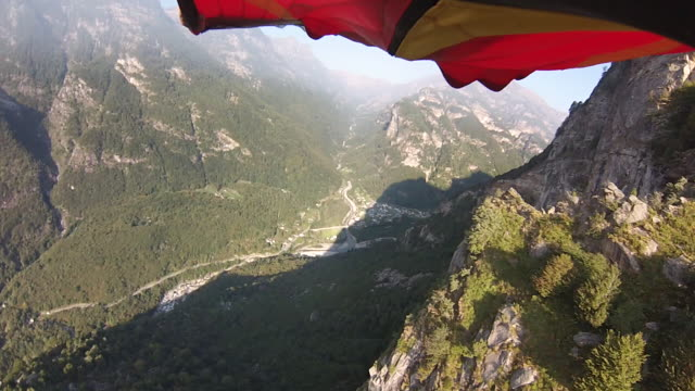 POV of wing suit flyer airbourne over mountains