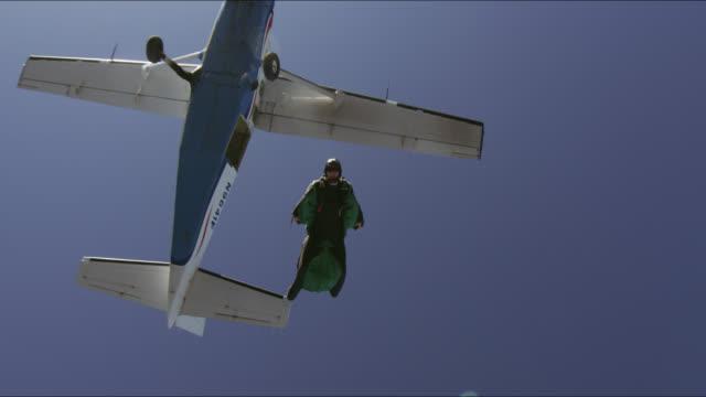 vídeos de stock, filmes e b-roll de wing suit pilot flies over hills - paraquedismo