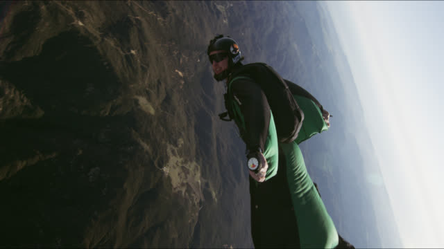 wing suit pilot flies over hills - stunt stock videos and b-roll footage