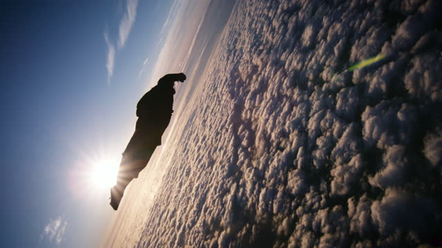 wing suit skydiving over beautiful clouds at sunset - animal wing stock videos & royalty-free footage