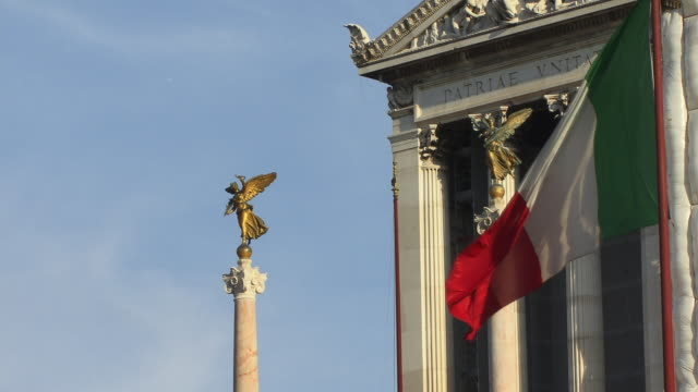 cu, winged figures on top of columns of national monument of victor emmanuel ii, italian flag in foreground, rome, italy - italian flag stock videos and b-roll footage