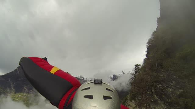 wingsuit flier descends from mountain summit, stormy weather - wearable camera stock videos & royalty-free footage