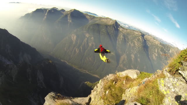 Wingsuit flier descends from mountain summit