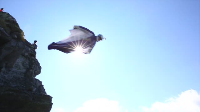 Wingsuit flier in mid air flight from mountain summit
