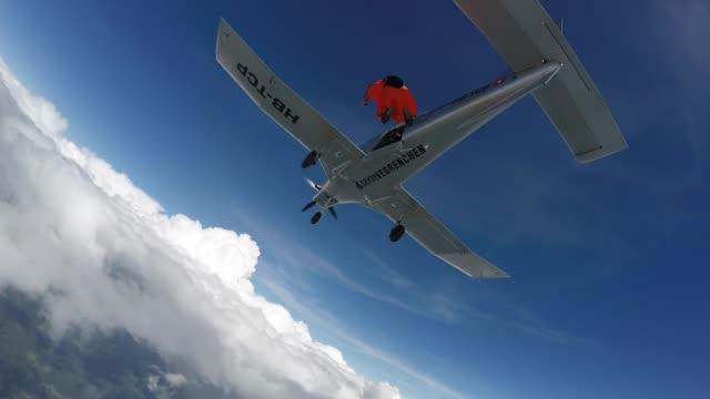 wingsuit-flieger springen vom flugzeug über die schweizer berge und ackerland - herausforderung stock-videos und b-roll-filmmaterial