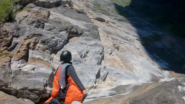 vidéos et rushes de wingsuit flier jumps from high platform, descends along cliff - parachute