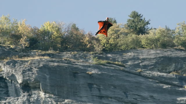 wingsuit flier jumps, then sail past rock cliff aerial flight - glider stock videos & royalty-free footage