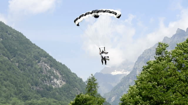 Wingsuit flier lands with parachute in mountain meadow