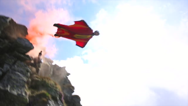 vidéos et rushes de wingsuit flier plunges from mountain summit, trailing smoke - sports extrêmes